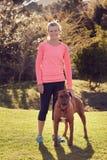 Hogere vrouw in openlucht in atletische slijtage met haar huisdierenhond royalty-vrije stock afbeelding
