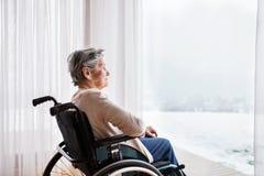 Hogere vrouw in rolstoel thuis royalty-vrije stock afbeeldingen