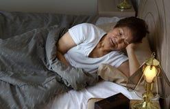 Hogere vrouw rusteloos bij nacht terwijl het proberen aan slaap royalty-vrije stock afbeelding