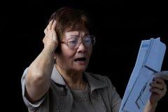 Hogere vrouw in spanning van financiële rekeningen op zwarte achtergrond royalty-vrije stock afbeeldingen