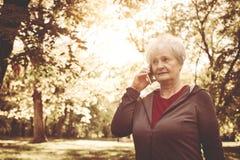 Hogere vrouw in sportkleding die zich in park en bespreking bevinden stock fotografie