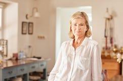 Hogere vrouw thuis met een ernstige gelaatsuitdrukking royalty-vrije stock afbeeldingen