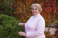 Hogere vrouw in tuin Stock Afbeelding