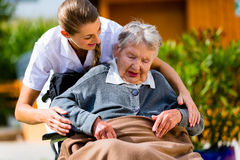 Hogere vrouw in verpleeghuis met verpleegster in tuin royalty-vrije stock afbeeldingen