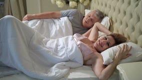 Hogere vrouw in zich bed het uitrekken en ontwaken stock videobeelden