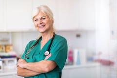 Hogere vrouwelijke arts die bij de camera glimlachen stock foto's