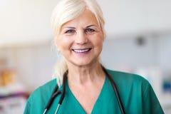 Hogere vrouwelijke arts die bij de camera glimlachen royalty-vrije stock foto's