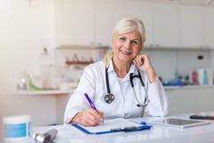 Hogere vrouwelijke arts die bij de camera glimlachen stock afbeeldingen
