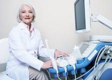 Hogere vrouwelijke arts die terwijl de machine van de vestigingsultrasone klank glimlachen Stock Fotografie