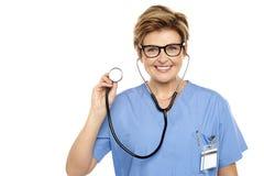 Hogere vrouwelijke arts klaar om u te onderzoeken Royalty-vrije Stock Afbeeldingen
