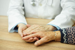 Hogere vrouwelijke hand - die door medelevende Arts wordt gehouden stock afbeelding
