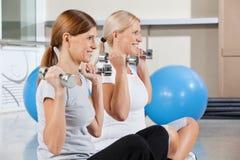 Hogere vrouwen die domoren in gymnastiek gebruiken stock foto's
