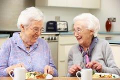 Hogere vrouwen die van maaltijd samen thuis genieten royalty-vrije stock foto's