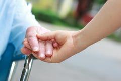 Hogere vrouwen in rolstoel holdingshanden stock fotografie