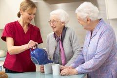 Hogere vrouwen thuis met werker uit de hulpverlening Stock Fotografie