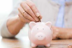 Hogere vrouwenhand die geld zetten aan spaarvarken Stock Foto