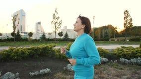 Hogere vrouwenlooppas bij park stock video