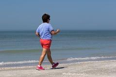 Hogere vrouwenmacht die op een strand lopen Stock Foto's