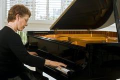 Hogere vrouwenpianist Stock Afbeeldingen