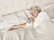 Hogere vrouwenslaap in bed Stock Foto's
