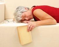 Hogere vrouwenslaap op bank Stock Afbeeldingen