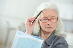 Hogere vrouwenzitting bij lijst die kruiswoordraadsel voltooien Stock Afbeeldingen