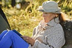 Hogere vrouwenzitting buiten een tent die een boek lezen stock foto's