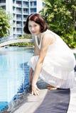 Hogere vrouwenzitting door pool royalty-vrije stock foto