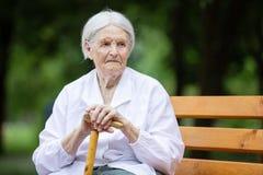 Hogere vrouwenzitting op bank in de zomerpark stock afbeeldingen