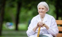 Hogere vrouwenzitting op bank in de zomerpark royalty-vrije stock fotografie
