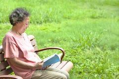 Hogere vrouwenzitting op bank en lezing een boek Stock Foto