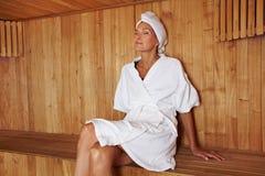 Hogere vrouwenzitting in sauna royalty-vrije stock afbeelding