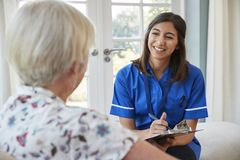 Hogere vrouwenzitting thuis met zorgverpleegster die nota's nemen stock foto