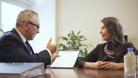 Hogere wettelijke agent die detail van hypotheekcontract verklaren om vrouw in makelaardijbureau te rijpen stock video