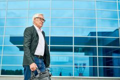 Hogere zakenman die aan het werk lopen stock fotografie