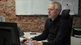 Hogere zakenman die bij computerzitting werken in zijn bureau stock footage
