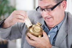 Hogere zakenman die geld opnemen aan een spaarvarken Royalty-vrije Stock Afbeelding