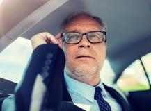 Hogere zakenman die smartphone in auto uitnodigen stock fotografie