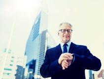 Hogere zakenman die tijd controleren op zijn polshorloge royalty-vrije stock fotografie