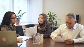 Hogere zakenman en rijpe onderneemster die contractdetails in advocaatbureau bespreken stock video