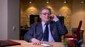 Hogere zakenman in formeel kostuum voor laptop spreken die blij op cellphone in bureau zijn stock video