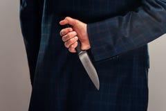 Hogere zakenman in kostuum met mes achter rug royalty-vrije stock afbeeldingen