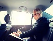 Hogere zakenman met documenten die in auto drijven stock afbeeldingen