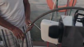 Hogere zeeman die zich achter een stuurwiel op sailboard bevinden De mens stuurt het schip in alleen open zee stock footage