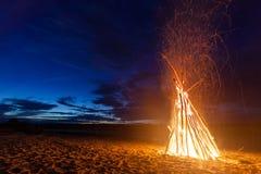 Hoguera brillante grande en la playa arenosa en la noche Foto de archivo libre de regalías