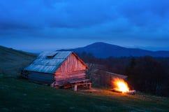 Hoguera cerca de una casa de madera en las montañas fotografía de archivo libre de regalías