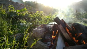 Hoguera de la cámara lenta que quema en campo turístico en la puesta del sol Montañas cárpatas almacen de metraje de vídeo