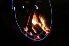 Hoguera en hoyo del fuego en el sitio para acampar Imagen de archivo