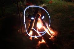 Hoguera en hoyo del fuego en el sitio para acampar Fotografía de archivo