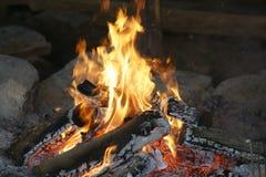 Hoguera en una hoguera con el fuego brillante que quema en la playa en la puesta del sol Imagen de archivo